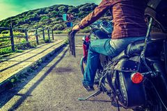 Girl on a classic motorcycle. On the edge of the road Royalty Free Stock Photo