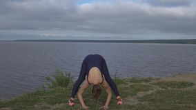 Woman in classical yoga pose, energy concentration. Girl in classical yoga pose, energy concentration, cloudy sky and lake on background. Yogi training, outdoor stock video footage