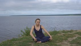 Girl in classical yoga pose, energy concentration. Cloudy sky and lake on background. Yogi training, outdoor meditation and healthy lifestyle stock video footage