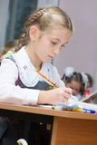 Girl in the classroom. Schoolgirl wrote in a notebook Royalty Free Stock Photography