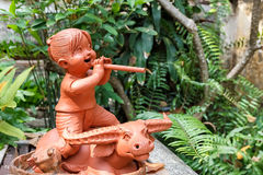 Girl Clay doll plays Recorder riding on buffalo Stock Photo