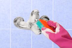 Girl clean the faucet with household chemicals and sponge. Background blue tile royalty free stock images