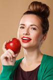 Girl with a clean skin holding a red apple. Royalty Free Stock Photography