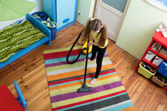 Girl cleaning floor with hoover Royalty Free Stock Photography