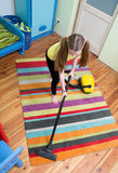 Girl cleaning floor with hoover Stock Photo