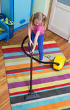 Girl cleaning floor with hoover Royalty Free Stock Photo