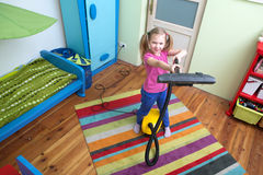 Girl cleaning floor with hoover Royalty Free Stock Images