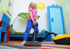 Girl cleaning floor with hoover Stock Photography
