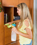 Girl cleaning furniture with cleanser and rag. In living room at home Stock Photography