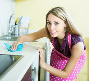 Girl cleaning furniture in kitchen Royalty Free Stock Images