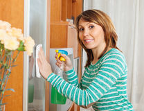 Girl cleaning glass door of furniture Royalty Free Stock Images