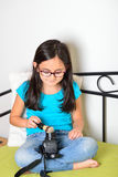 Girl cleaning her camera Royalty Free Stock Image