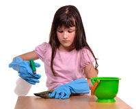 Girl cleaning her desk with cleaning supplies Royalty Free Stock Photography