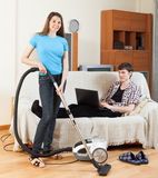Girl cleaning at home while man with notebook Stock Images
