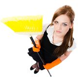 Girl cleaning the house - elevated view. Woman in orange rubber gloves cleaning the house with yellow broom - isolated on white background royalty free stock photography