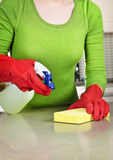 Girl cleaning kitchen. With sponge and rubber gloves stock image