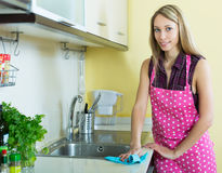 Girl cleaning kitchen Stock Photography