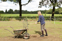 Girl cleaning the manure Stock Images