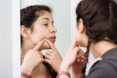 Girl cleaning pores. Young girl cleaning pores in front of mirror at home royalty free stock images