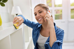 Girl cleaning and speaking on the phone Stock Photos