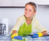 Girl cleaning surfaces in the kitchen Stock Photography