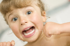 Girl cleaning teeth by dental floss royalty free stock images