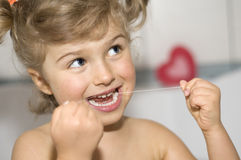Girl cleaning teeth by dental floss Royalty Free Stock Image