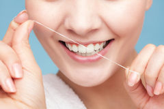 Girl cleaning teeth with dental floss. Health care. Part of female face. Young woman smiling girl cleaning her white teeth with dental floss on blue. Daily Stock Photos