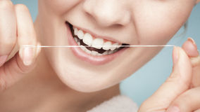Girl cleaning teeth with dental floss. Health care. Part of female face. Young woman smiling girl cleaning her white teeth with dental floss on blue. Daily Royalty Free Stock Photography