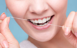 Girl cleaning teeth with dental floss. Health care Royalty Free Stock Image