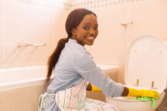 Girl cleaning toilet Stock Images
