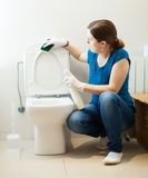 Girl cleaning toilet seat with sponge and cleaner Stock Photos