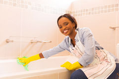 Girl cleaning up bathtub Royalty Free Stock Image