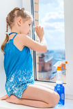 Girl cleaning a window with cloth and detergent Stock Image