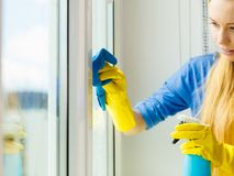 Girl cleaning window at home using detergent rag Royalty Free Stock Photos