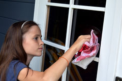 Girl cleaning windows stock image