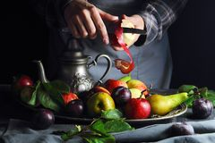 Girl cleans the Apple. Over a bowl of fruit Stock Images