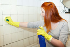 Girl cleans bathroom with sponge Stock Images
