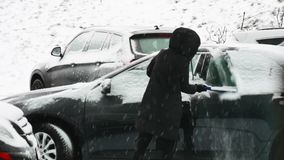 Girl cleans the car from the snow stock footage