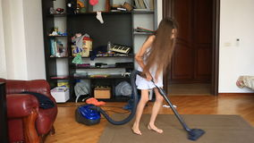 The girl cleans the carpet in the room with a vacuum cleaner stock footage
