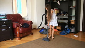 The girl cleans the carpet in the room with a vacuum cleaner stock video footage