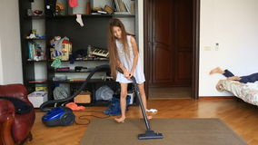 The girl cleans the carpet in the room with a vacuum cleaner stock video