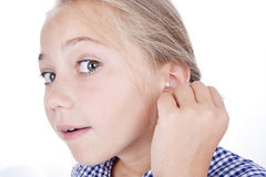 Girl cleans ear. Little beatiful girl cleans ear stock image