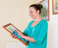 Girl cleans picture in her house Royalty Free Stock Image
