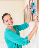 Girl cleans picture in her house Royalty Free Stock Photos