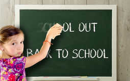 A girl clears school out on blackboard. A girl clears school out on green blackboard Royalty Free Stock Photos