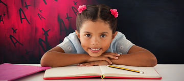 Composite image of girl clenching teeth while leaning on book. Girl clenching teeth while leaning on book against black background Stock Photography