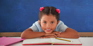 Composite image of girl clenching teeth while leaning on book Stock Images