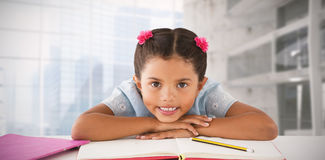 Composite image of girl clenching teeth while leaning on book Royalty Free Stock Photos