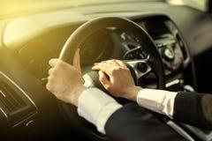 The girl clicks on the car signal. The girl clicks a hand on the signal on the steering wheel of the car stock photography